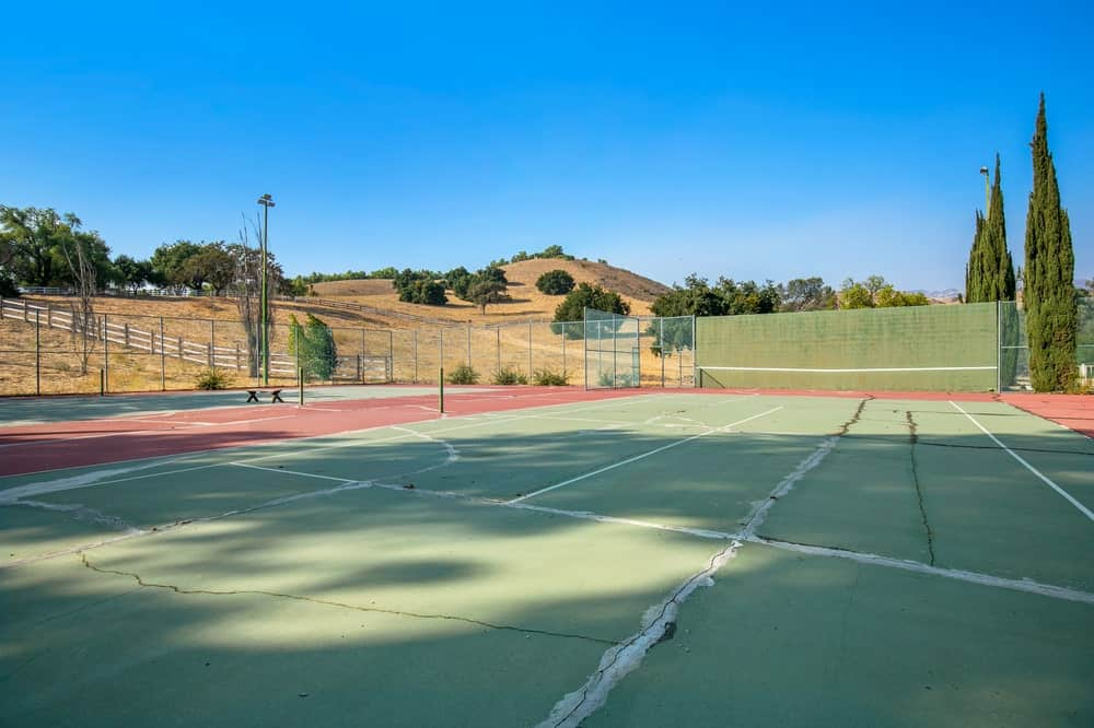 The recreation area of the ranch also has a professional-size tennis court adorned with tall pines in the background. Image courtesy of Toptenrealestatedeals.com.