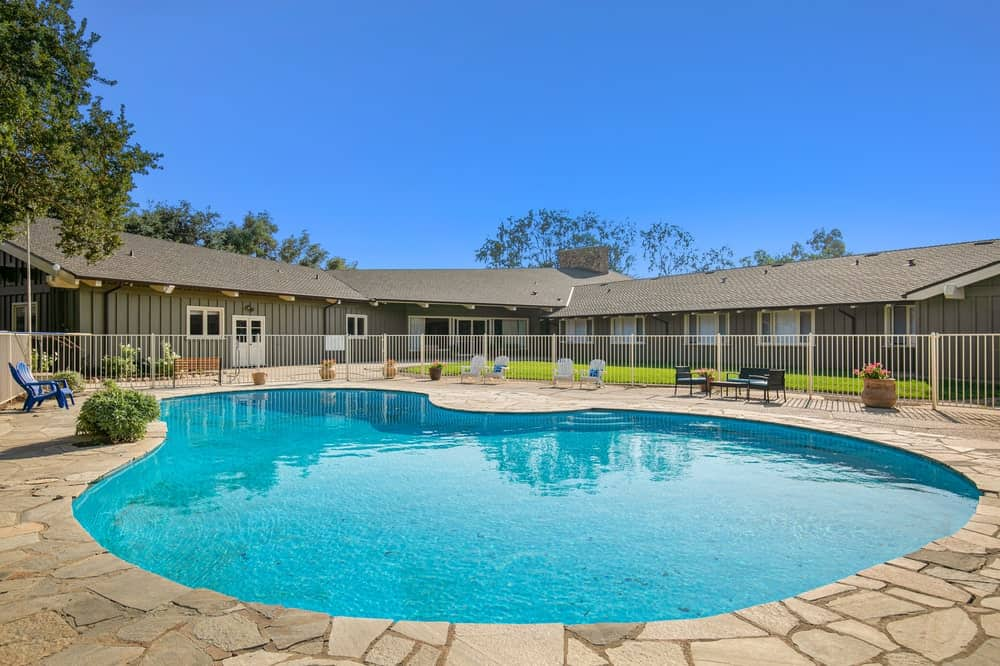 The recreation area also has a pool surrounded by walkways of mosaic beige stone fitted with lounge chairs and bordered with white railings. Image courtesy of Toptenrealestatedeals.com.