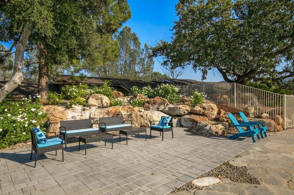 This is a close look at the poolside area that has various sitting areas and a landscaping background of stone and shrubs. Image courtesy of Toptenrealestatedeals.com.