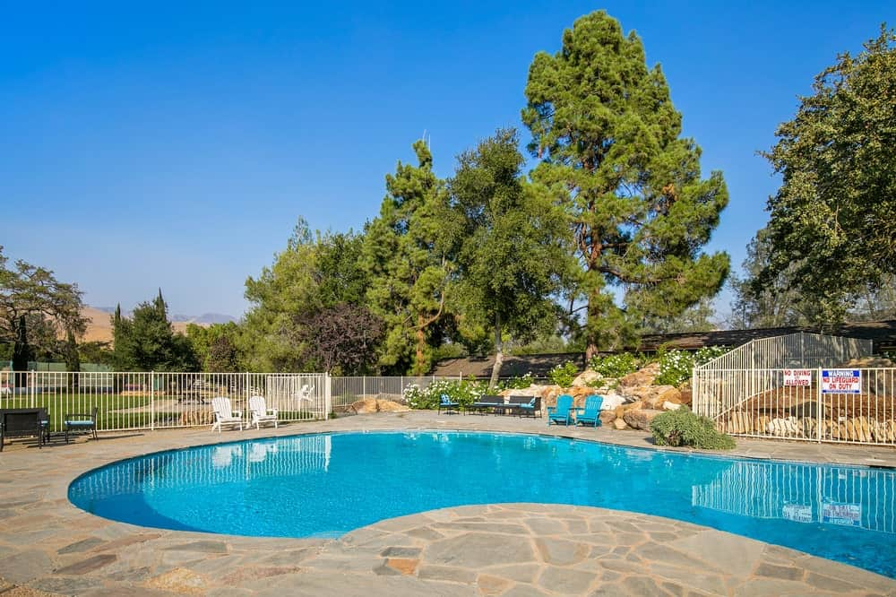 This is the other view of the pool with a background of tall trees that bring complement and shade to the area. Image courtesy of Toptenrealestatedeals.com.