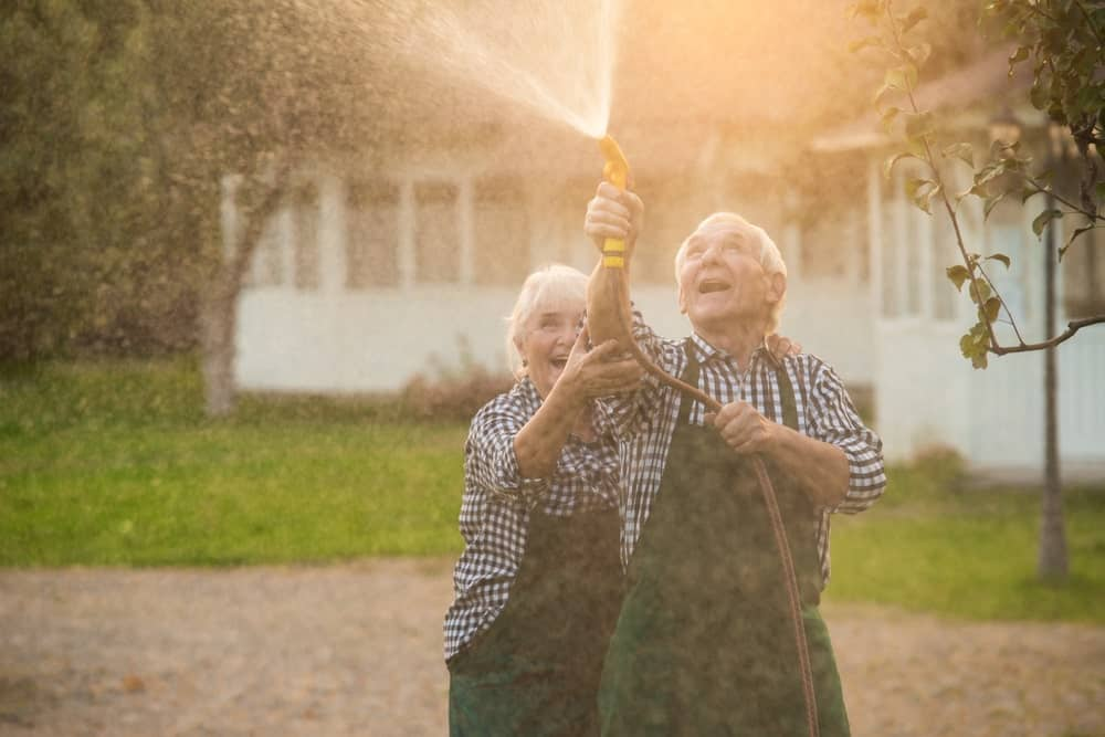 An elderly couple playing with a garden hose.