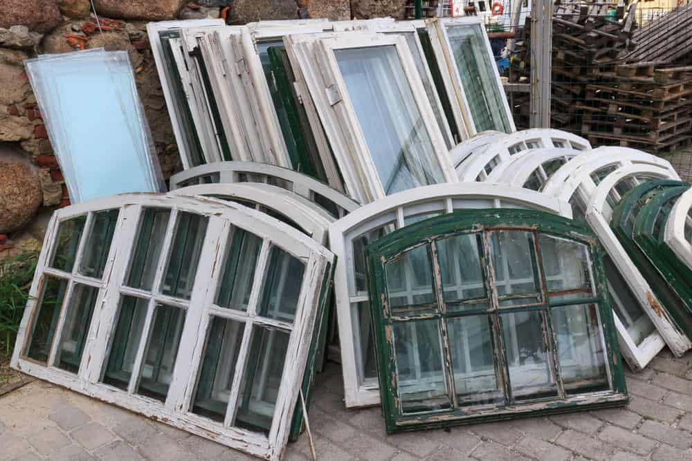 A pile of various old window frames.