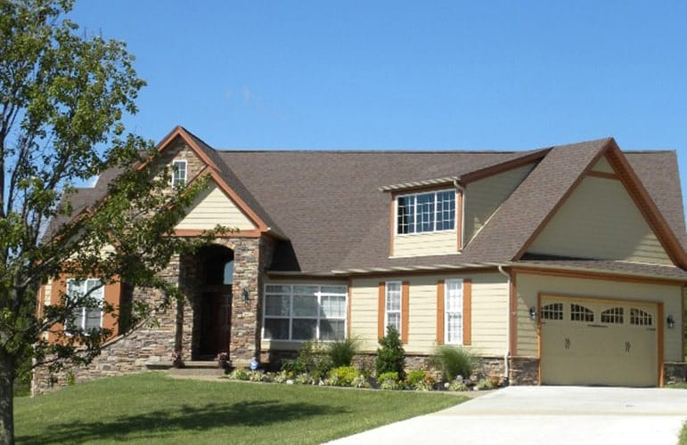 Front exterior view showing the stone accents, angled garage, shed dormer, and yellow siding lined with rustic wood trims.