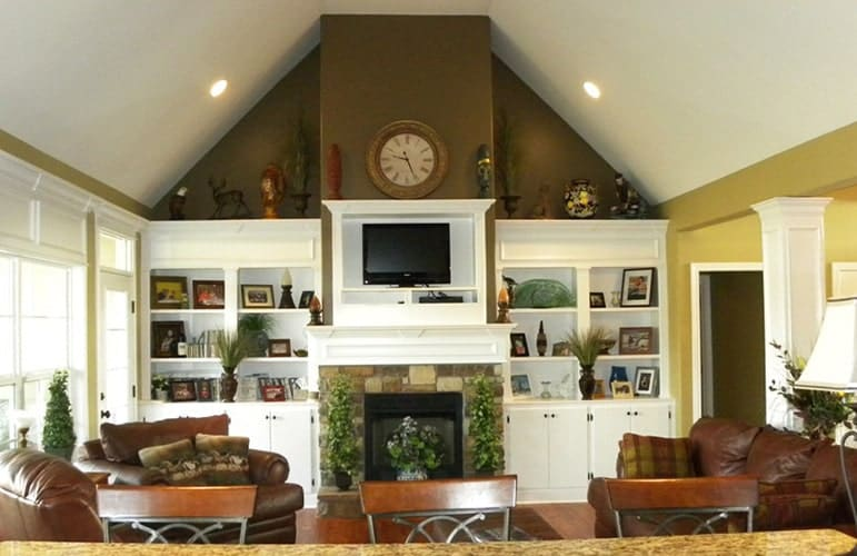 The living room has a vaulted ceiling, white built-ins, leather seats, and a stone fireplace with a TV on top.