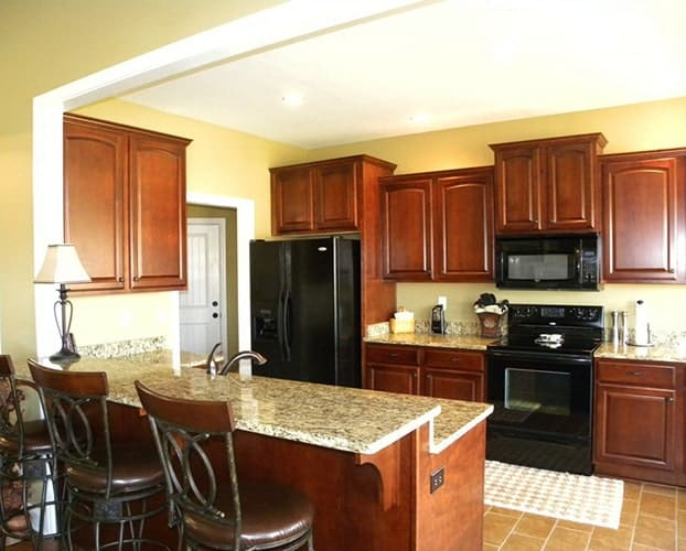 The kitchen is equipped with granite countertops, black appliances, wooden cabinetry, and a two-tier peninsula.