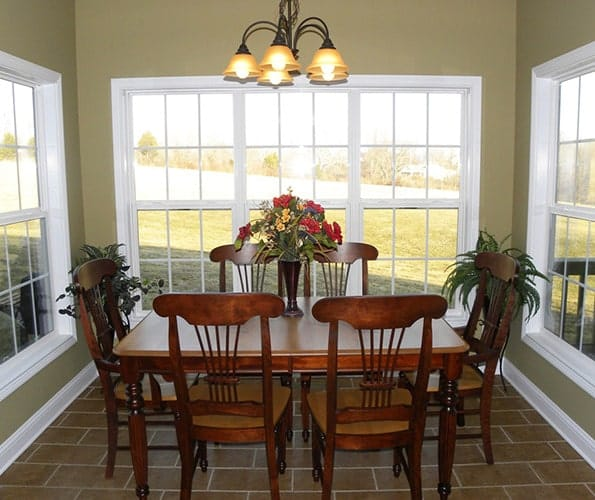 Breakfast room with cushioned chairs, wooden dining set, a warm glass pendant, and large framed windows surrounding the room.