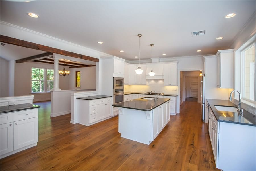 The kitchen is equipped with stainless steel appliances, white cabinetry, granite countertops, two sinks, and a large island.