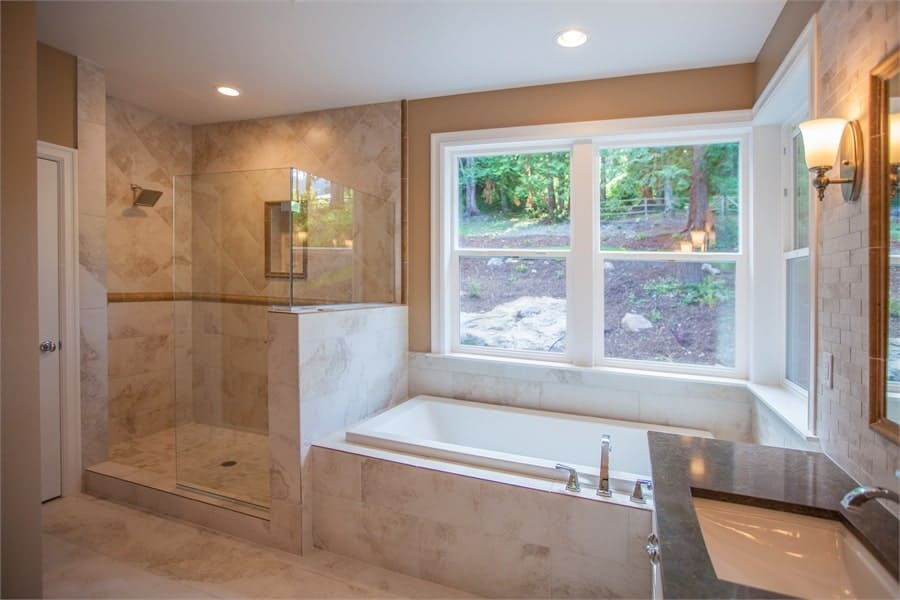 Primary bathroom with a walk-in shower and a drop-in bathtub placed under the picture window.