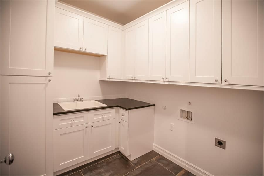 The laundry room is filled with white cabinets, a granite countertop, and a porcelain sink.