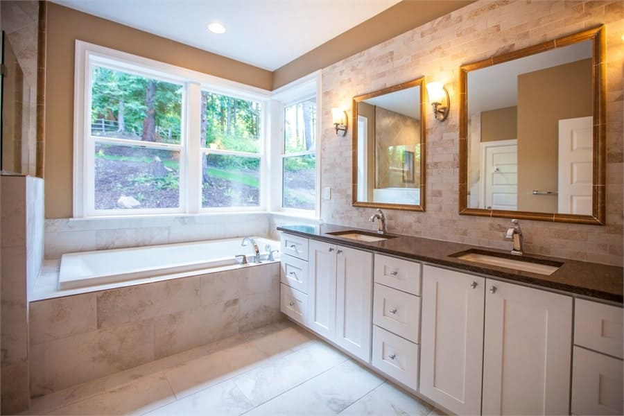 Large vanity with two sinks and decorative mirrors complete the primary bathroom.