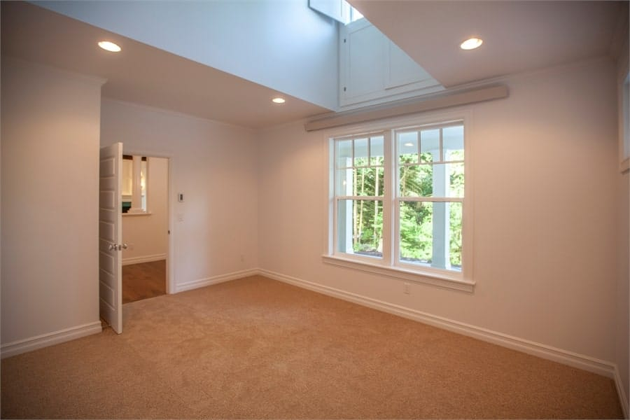 A white door opens to a bedroom with white walls and beige carpet flooring.