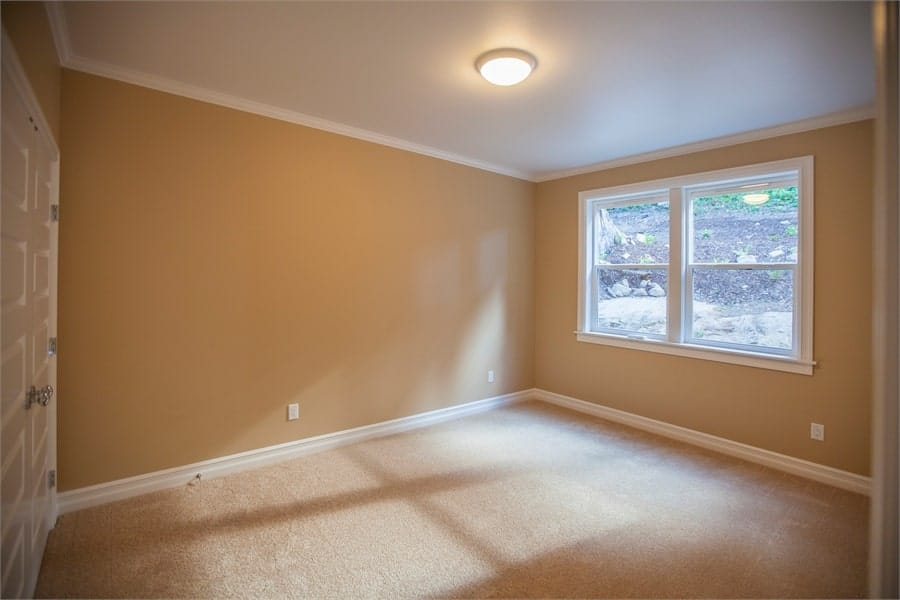 Bedroom with beige walls, carpet flooring, and a white framed window.