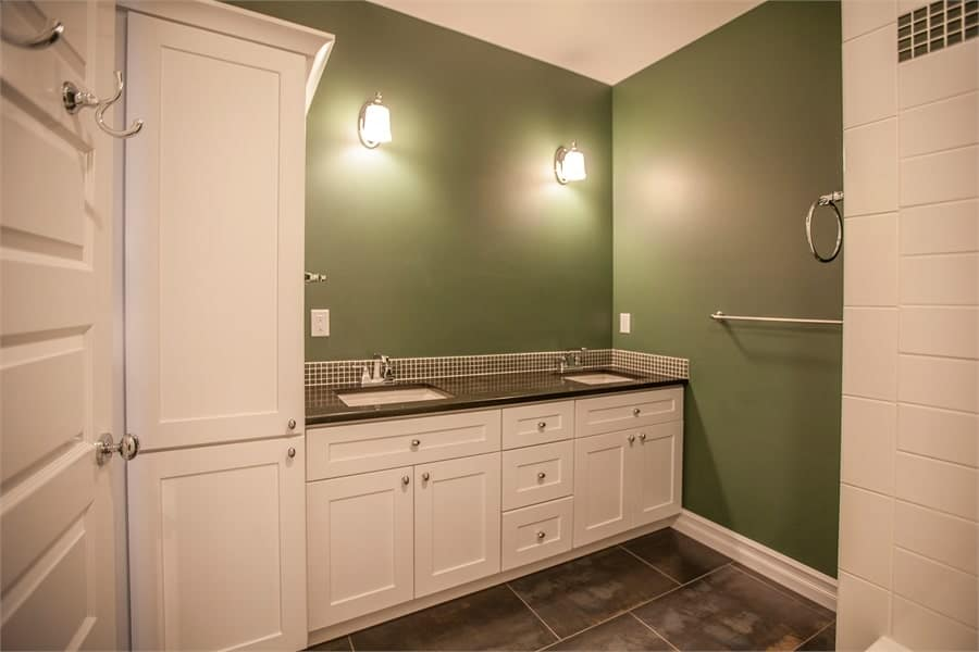 Bathroom with green walls and a dual sink vanity illuminated by glass sconces.