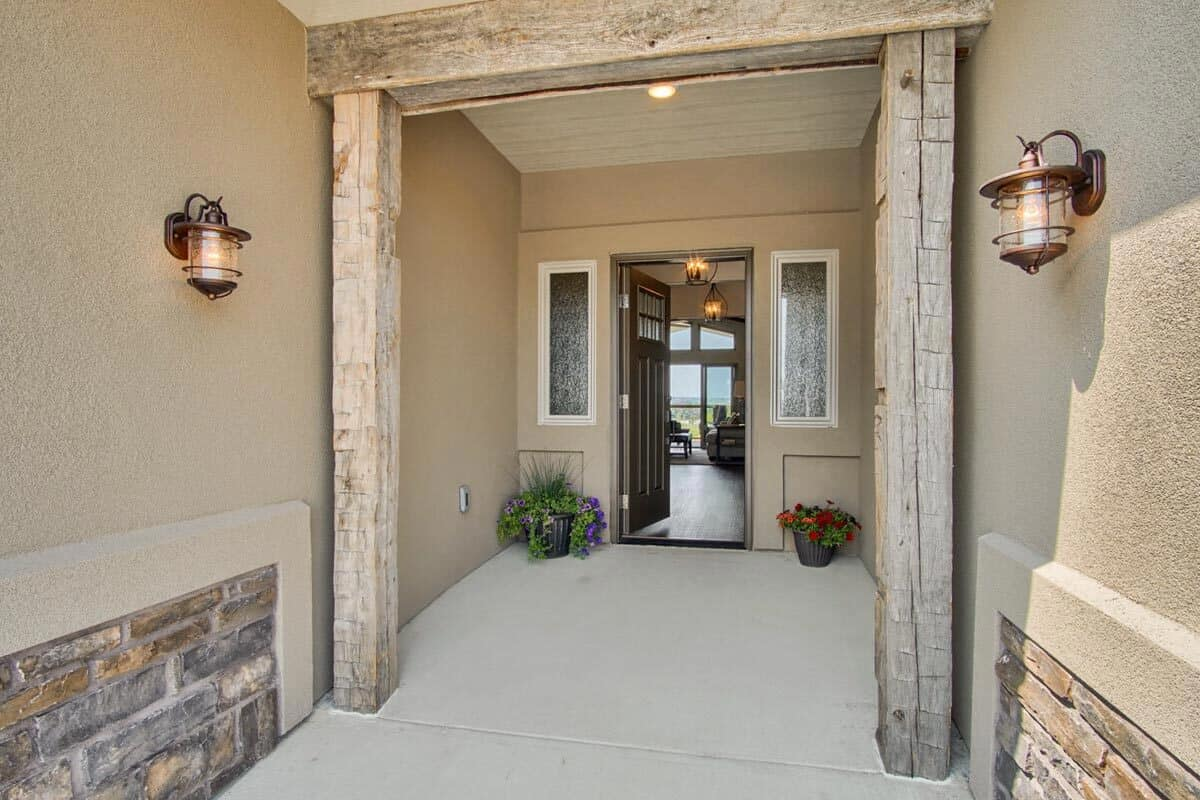 Glass sconces along with fresh potted plants grace the entry patio.