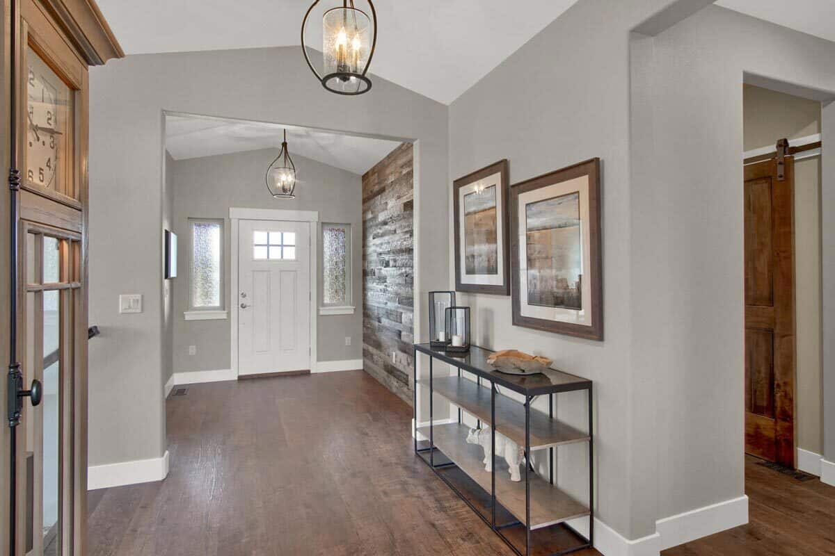 The foyer includes a white entry door and a wood-paneled accent wall.