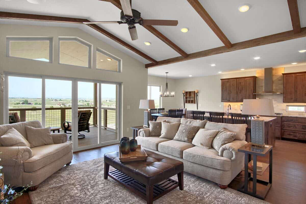 An open layout view showing the living room, kitchen, and dining area with views of the expansive yard.