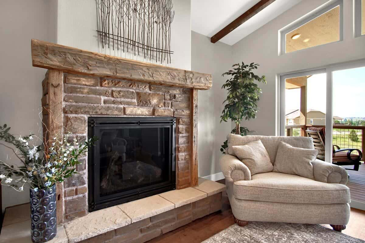 The brick fireplace is complemented with a beige armchair and green potted plants.