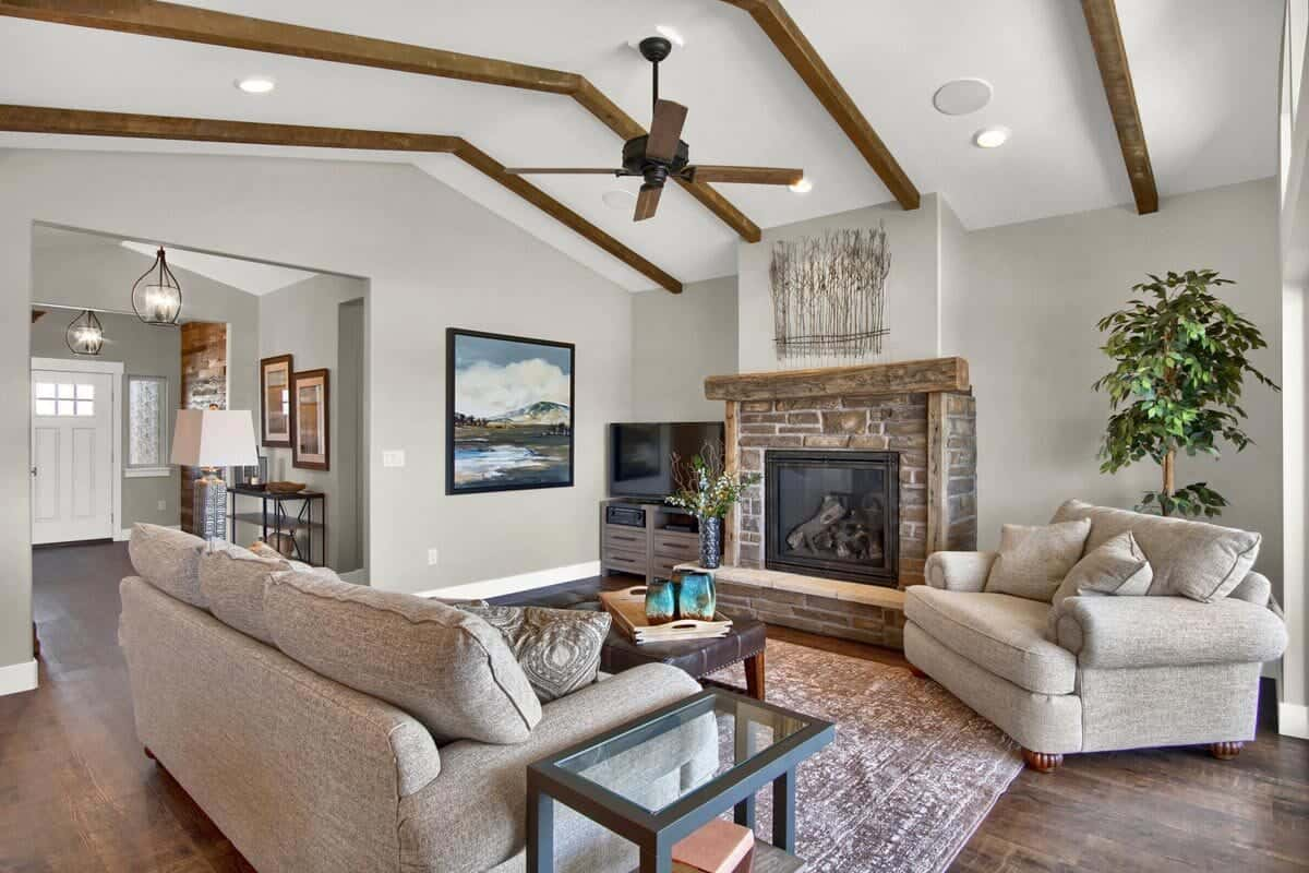 A vaulted ceiling framed with exposed wood beams tops the living room.