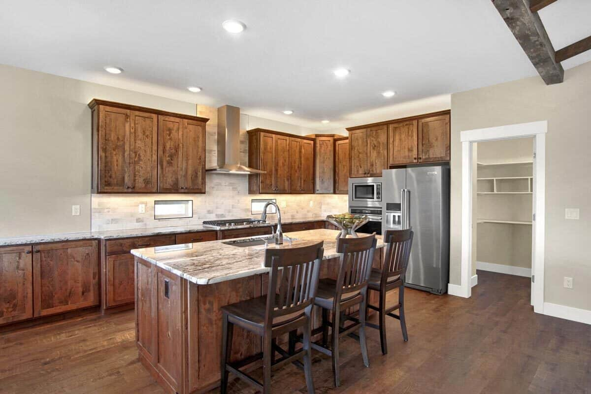 The kitchen is equipped with slate appliances, natural wood cabinetry, subway tile backsplash, and a breakfast island.