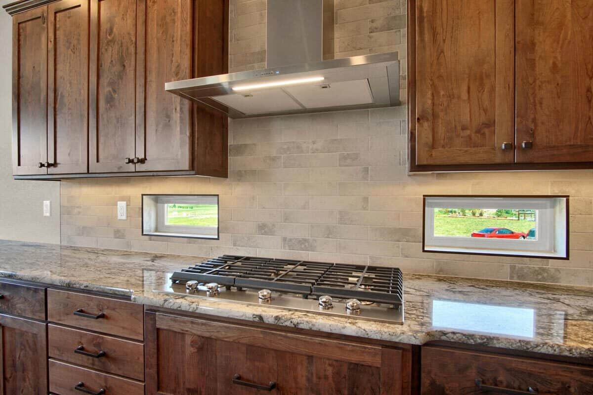 A close-up look at the built-in cooktop nestled in between the cabinets and small glass windows.
