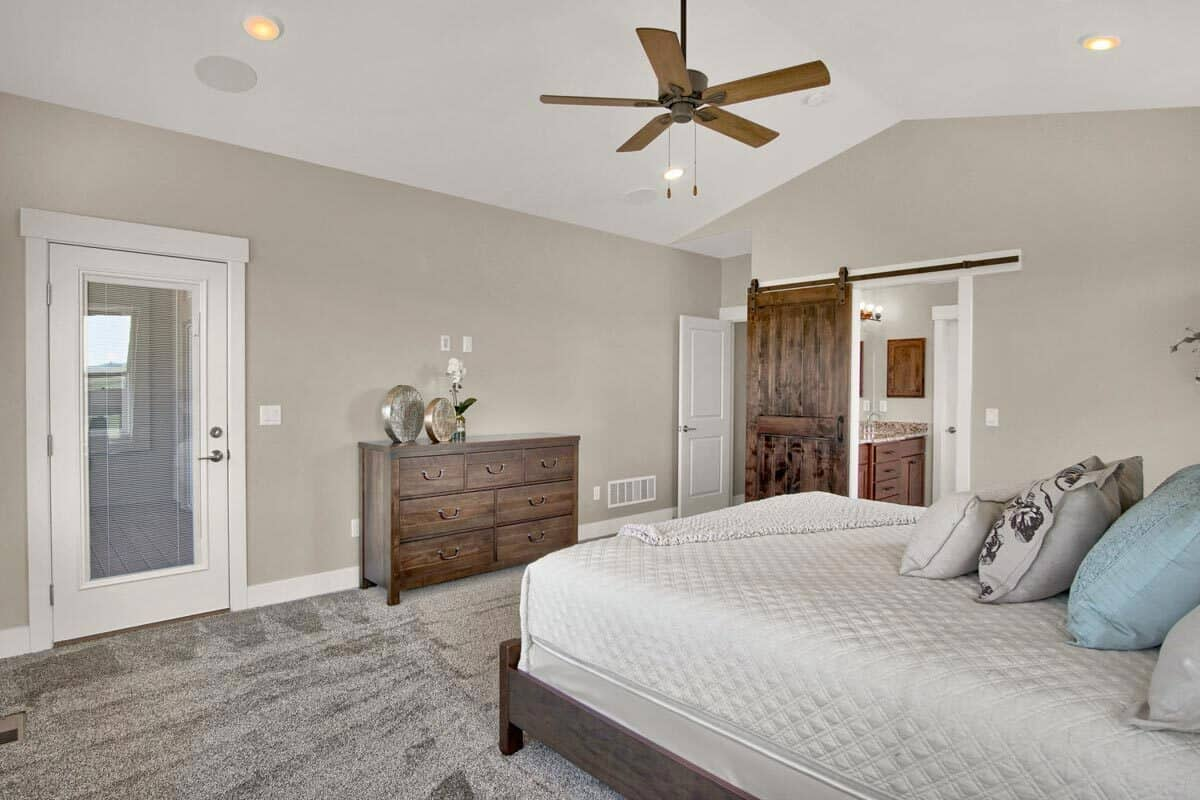 Wooden furnishings and a brushed copper ceiling fan complete the primary suite.