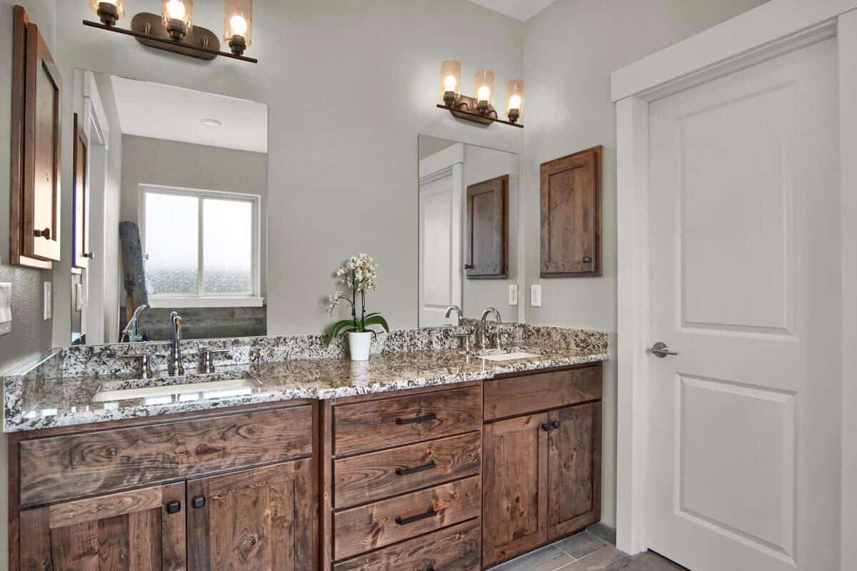 The dual sink vanity is paired with frameless mirrors and warm glass sconces.