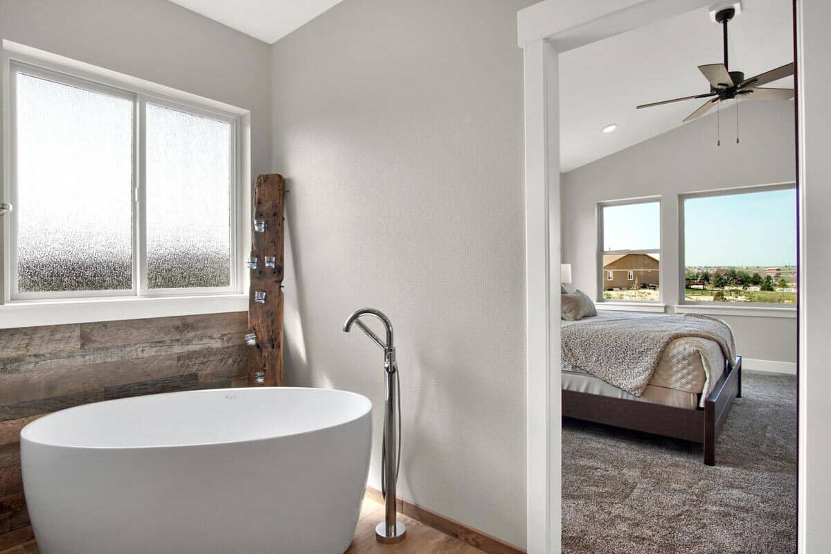 The freestanding tub with a chrome faucet is placed under the frosted glass windows.
