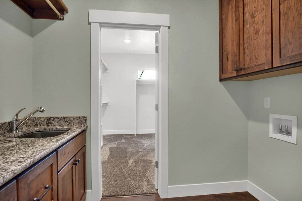 The primary bathroom opens to a walk-in closet with carpet flooring.
