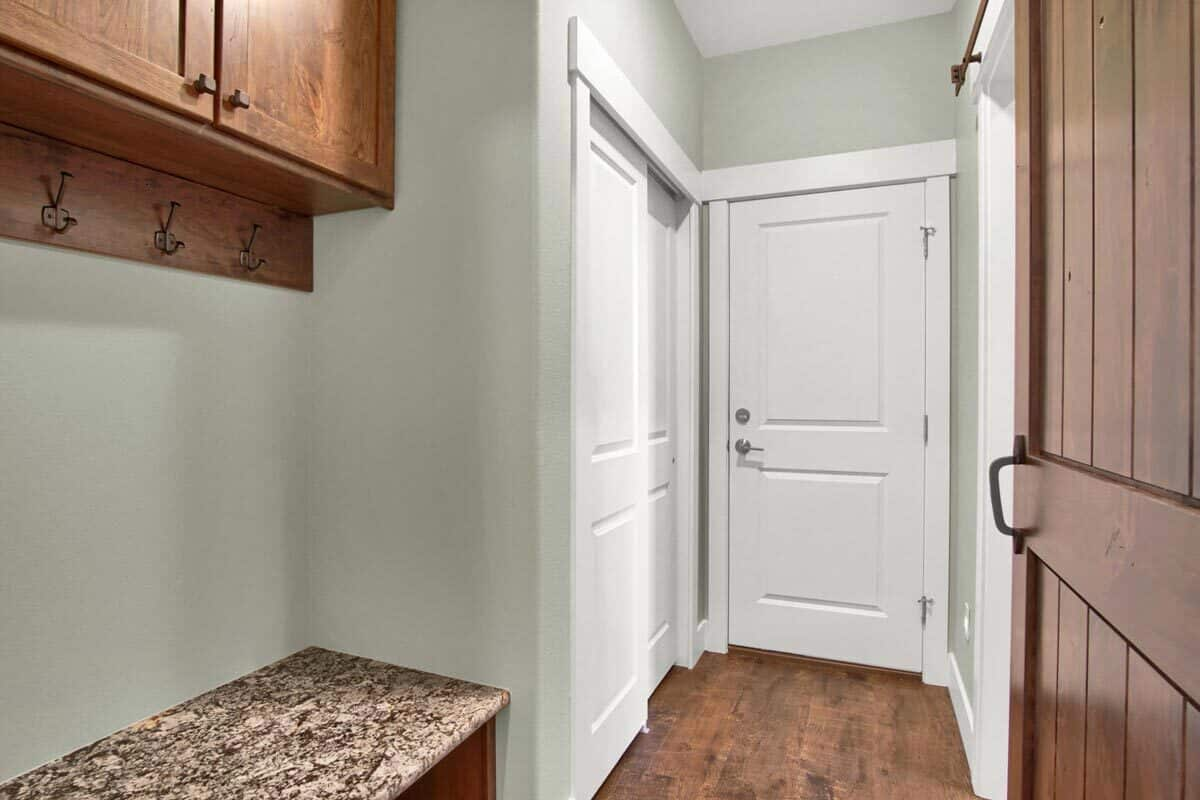 Mudroom with wooden cabinets, built-in bench, and a coat hook rack.