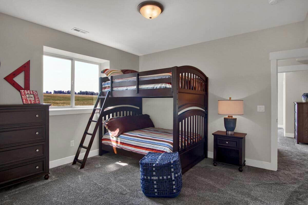 This bedroom is furnished with a bunk bed, a dark wood dresser, a nightstand, and a blue ottoman.