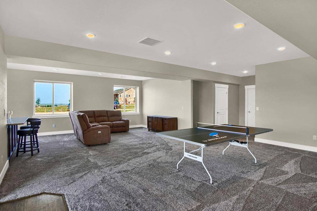 The recreation room is filled with a game table, a leather sectional, and a wet bar.