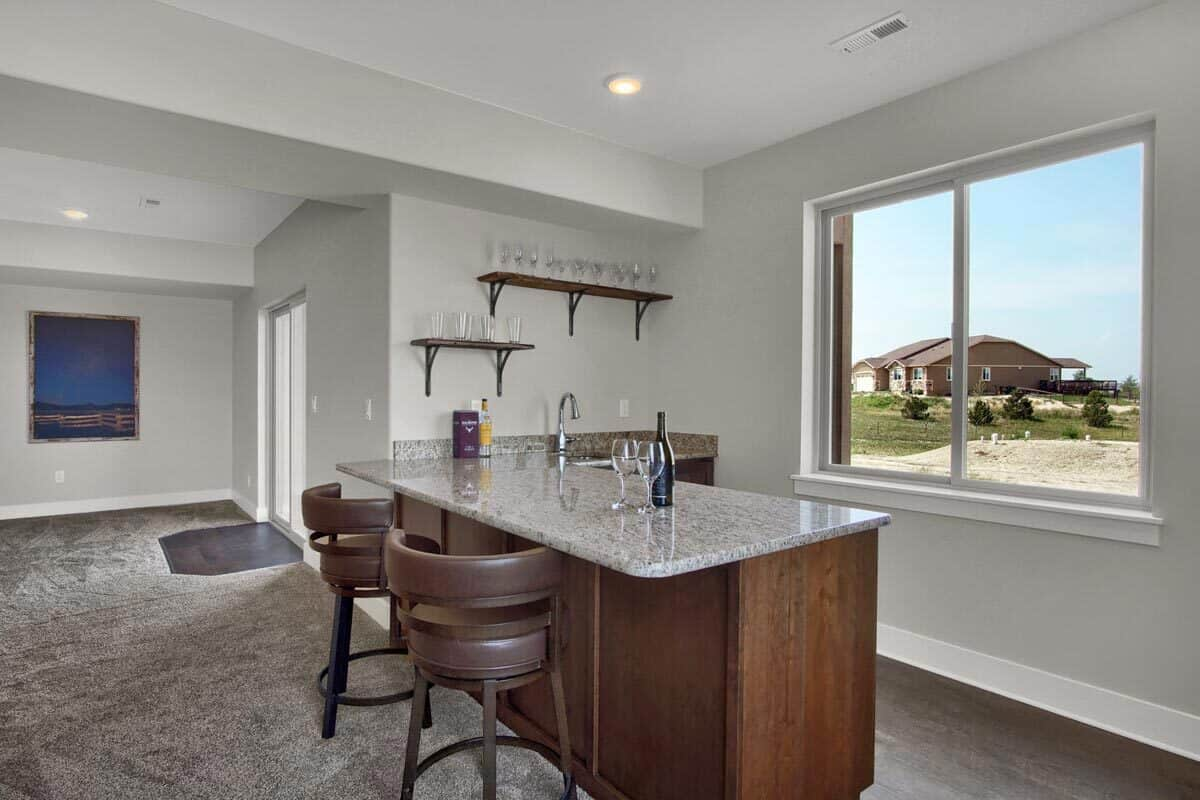 The wet bar has granite countertops, floating shelves, and a couple of round stools.