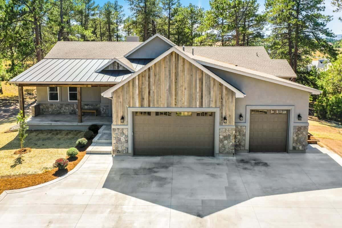 Front exterior view showing the three-car garage and a covered entry porch complemented with a concrete stoop.