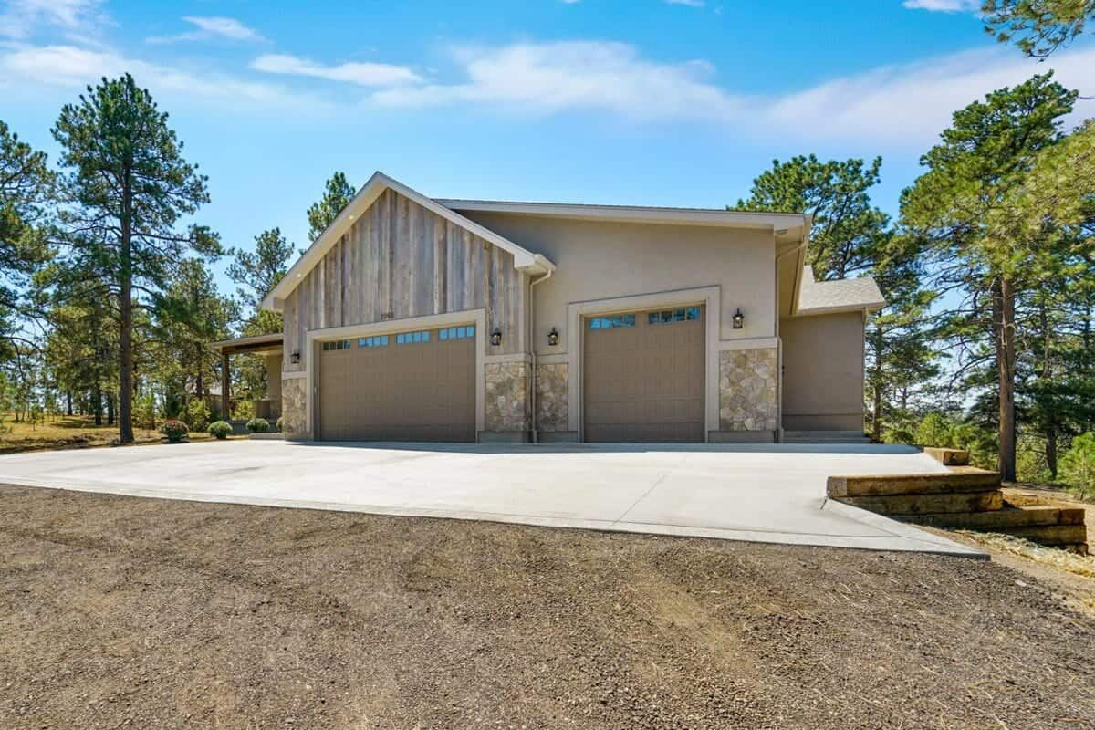 The three-car garage is clad in a barn wood exterior with stone accents.