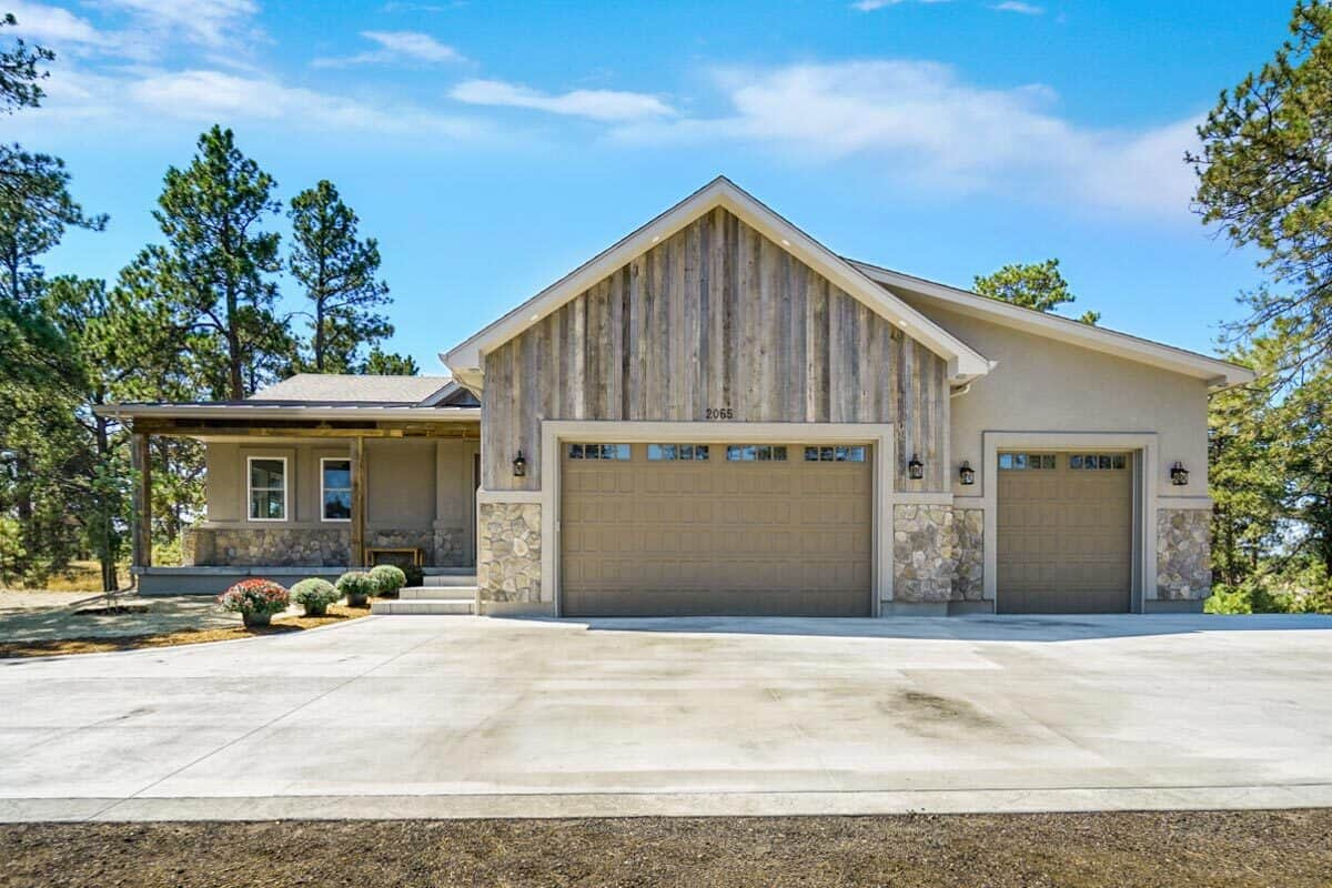 A concrete driveway complements the three-car garage.