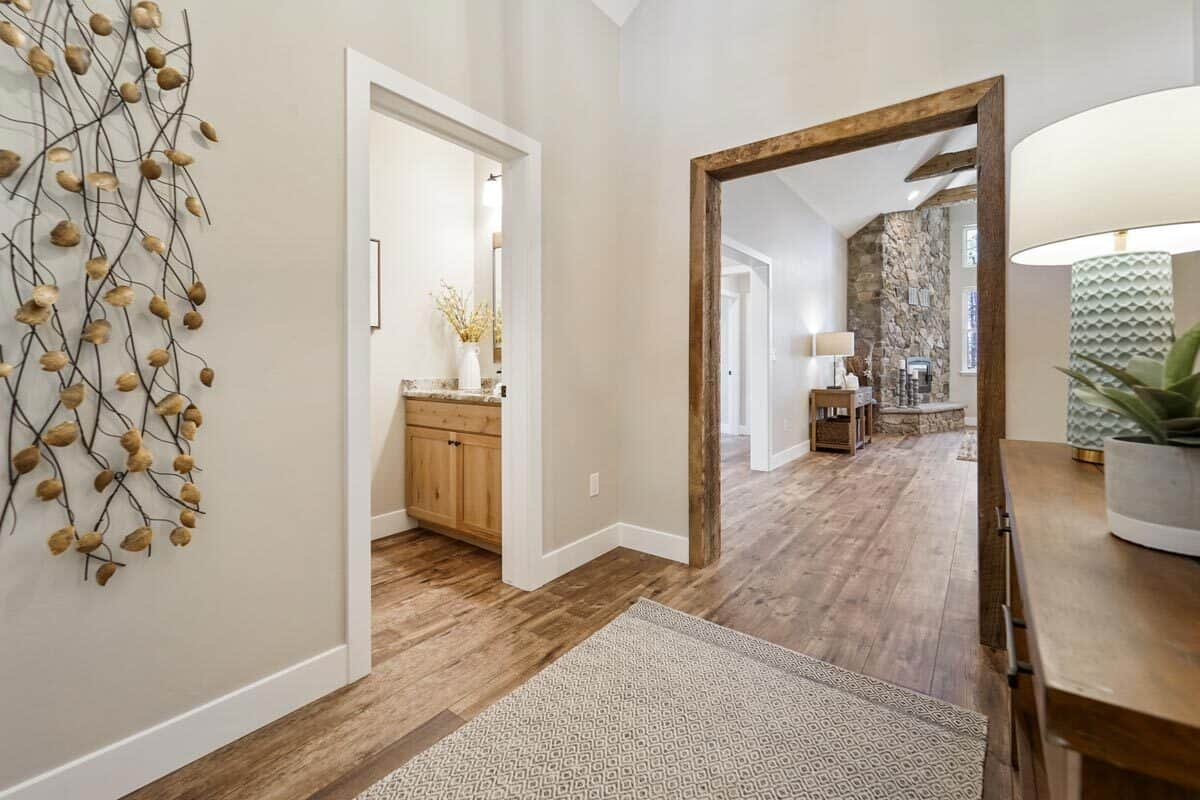 Foyer with a wooden cabinet, a patterned area rug, and a lovely wall decor adorning the beige walls.