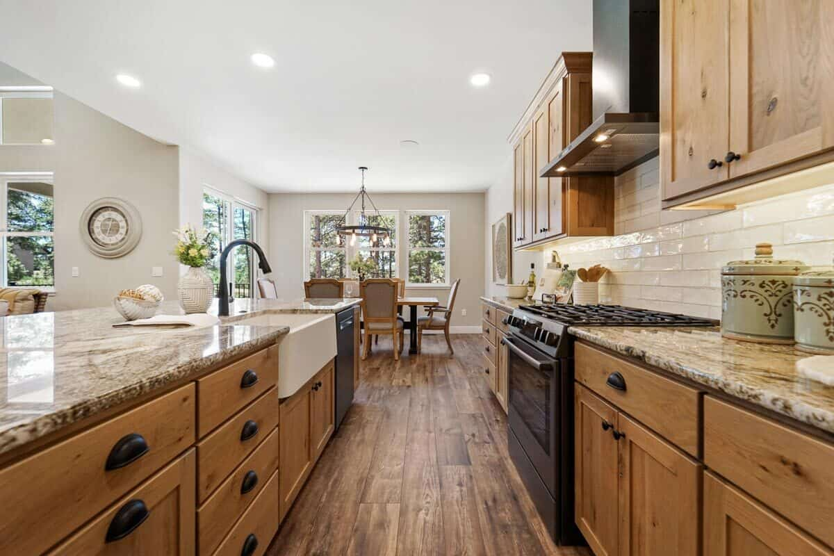 The breakfast island includes a farmhouse sink and a black dishwasher.
