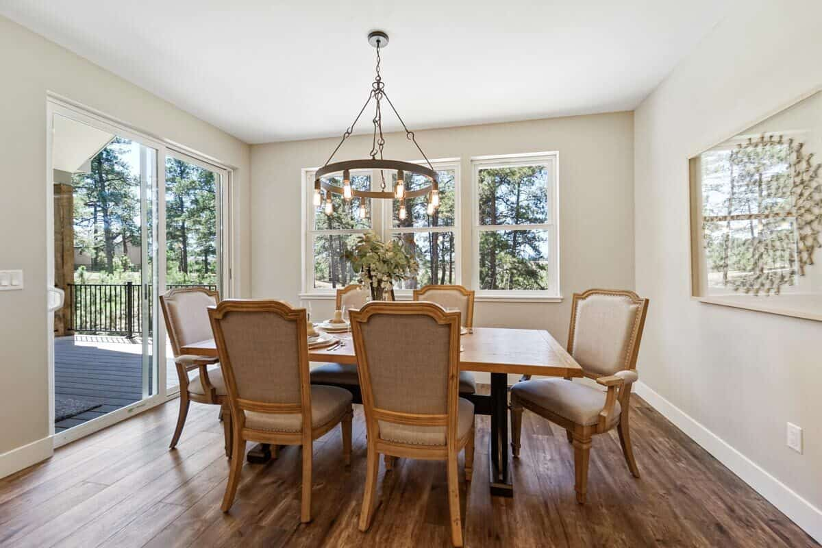 Dining area with a framed artwork and a wooden dining set well-lit by a round chandelier.