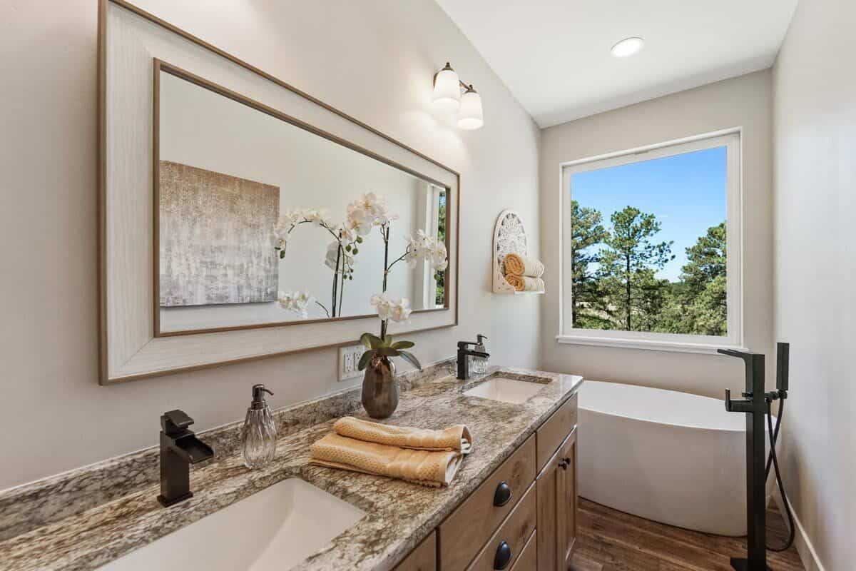 The primary bathroom has a dual sink vanity and a freestanding tub placed under the picture window.