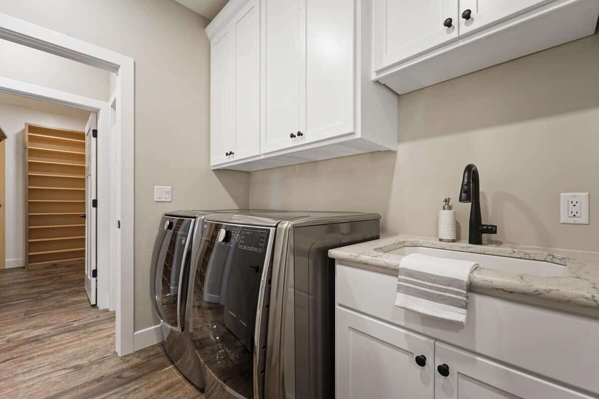 Utility room with slate laundry appliances, white cabinets, and sink vanity.
