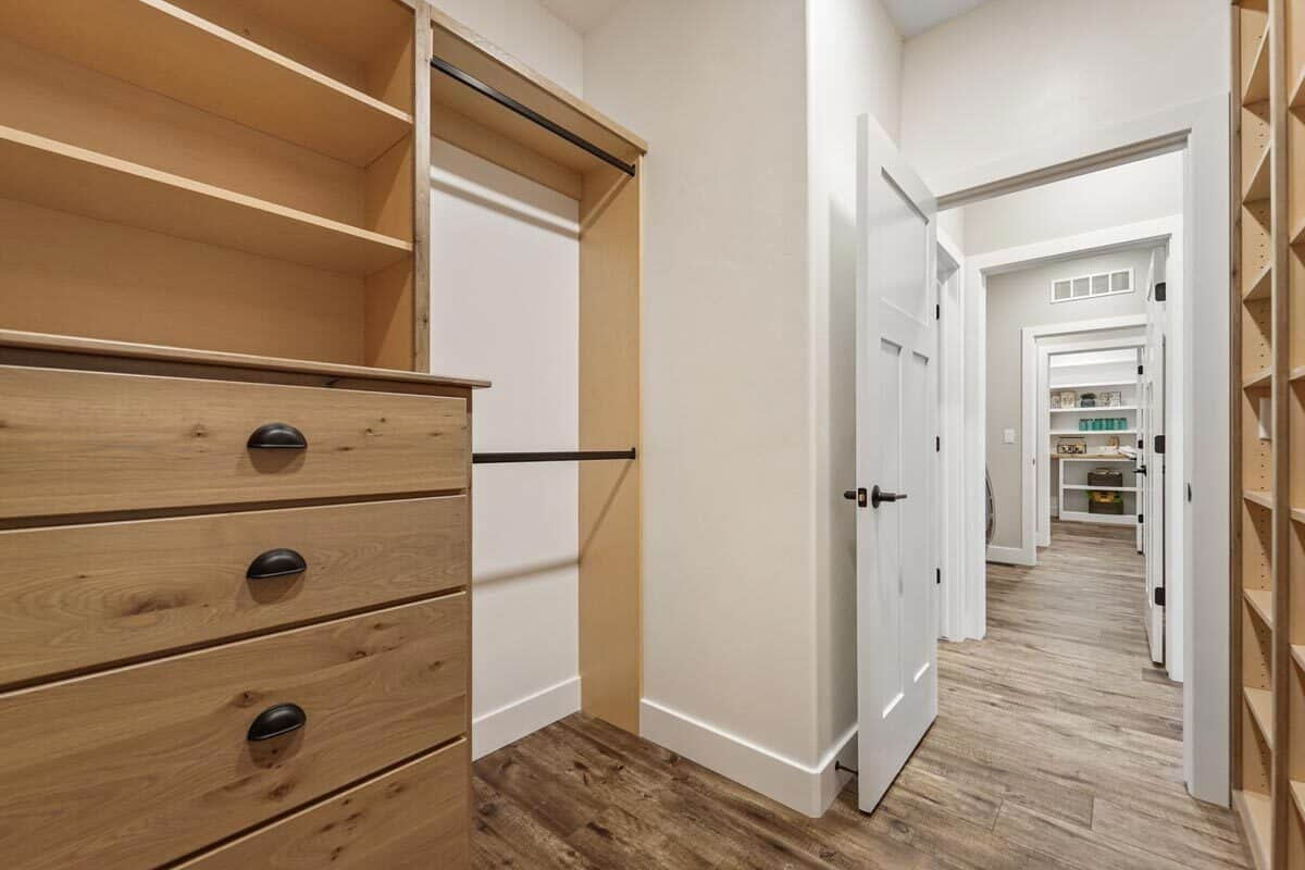 The walk-in closet is filled with wooden shelves and drawers.