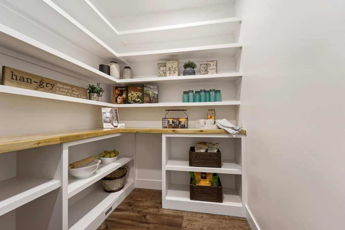 The walk-in pantry is filled with built-in white shelves and a wooden countertop.