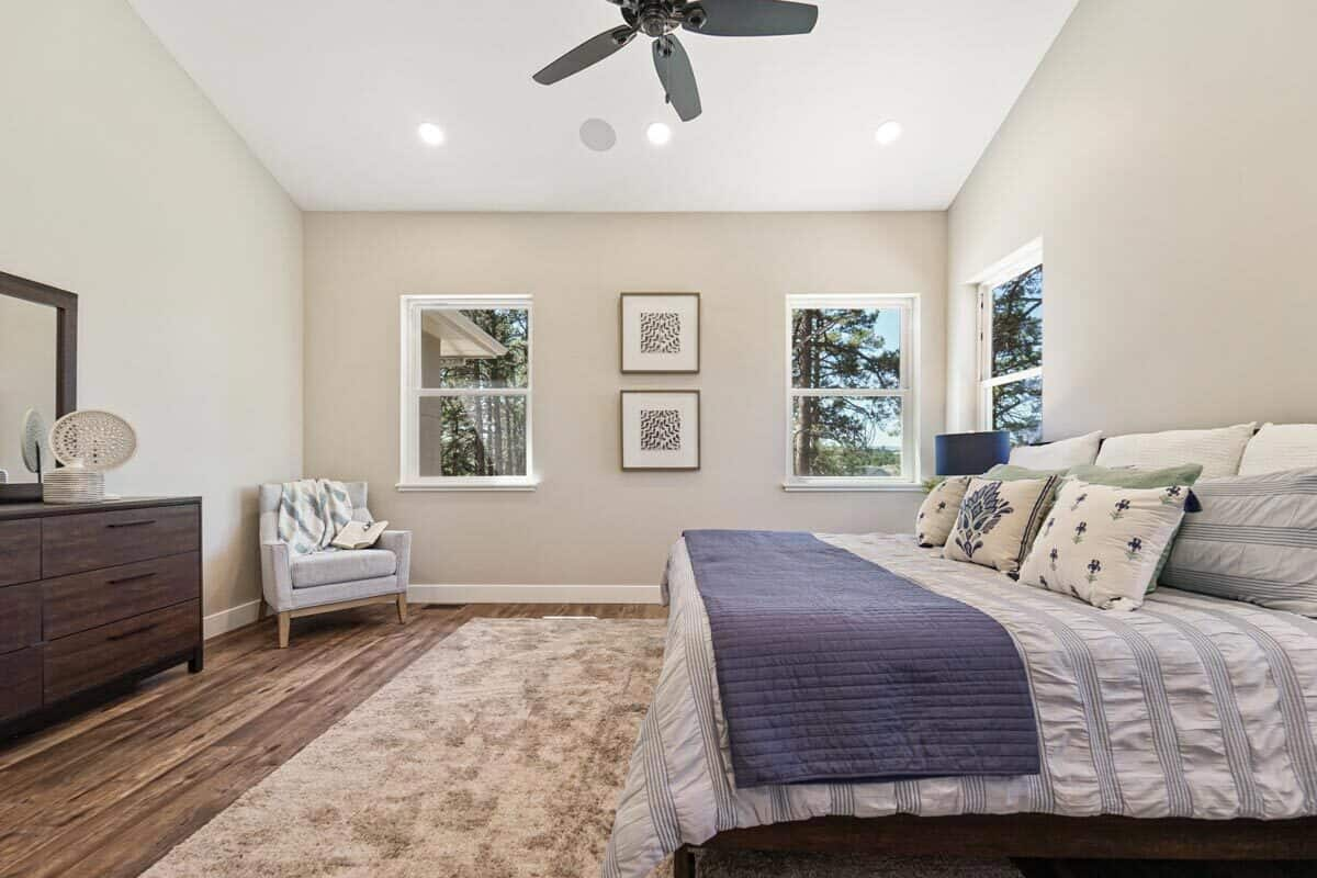 Recessed ceiling lights along with natural light from the white framed window brighten the primary bedroom.