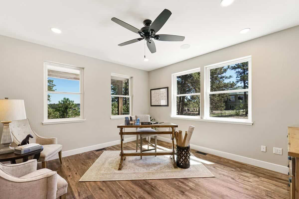 Home office with beige seats, wooden tables, and a black fan mounted against the regular ceiling.