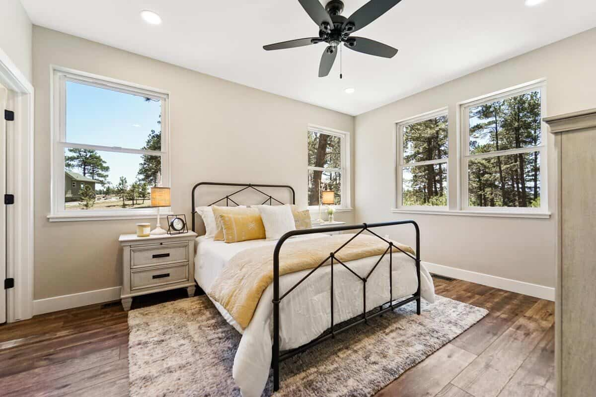 This bedroom offers a metal bed, white nightstands, and an area rug over wide plank flooring.