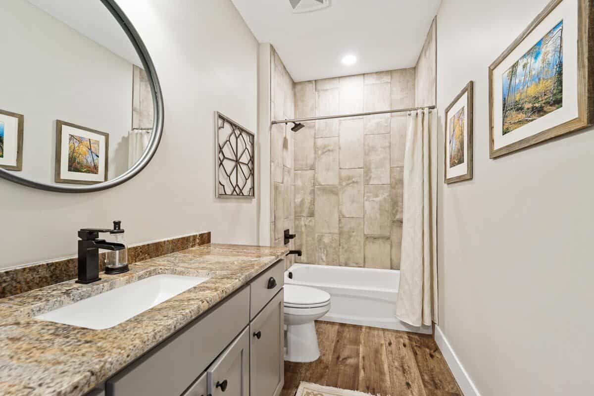 This bathroom is equipped with a granite top vanity, a toilet, and a tub and shower combo.