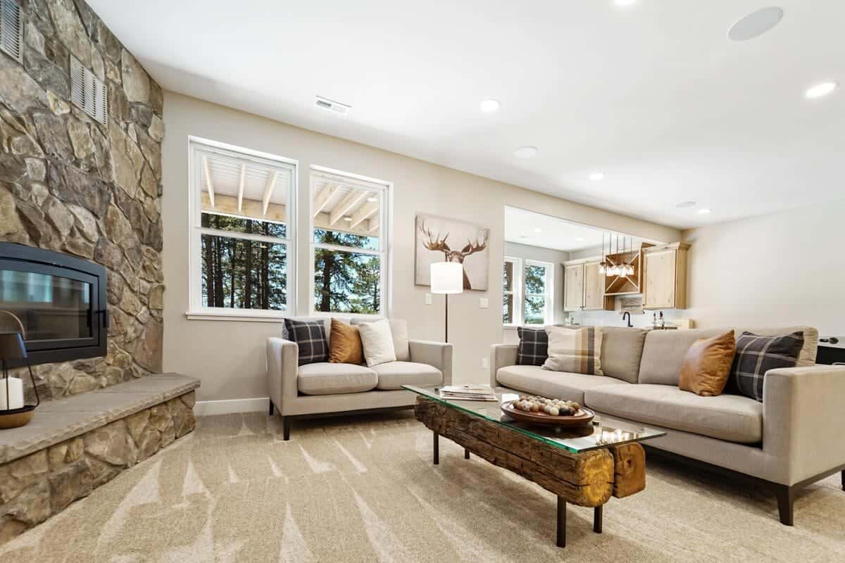 Recreation room with beige sectionals, a glass top coffee table, and a large stone fireplace.