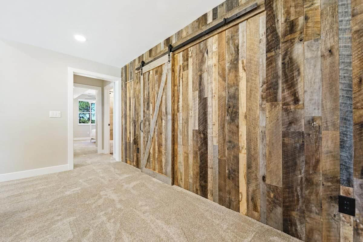 A sliding barn door leading to the mechanical room blends in with the wood-paneled accent wall.