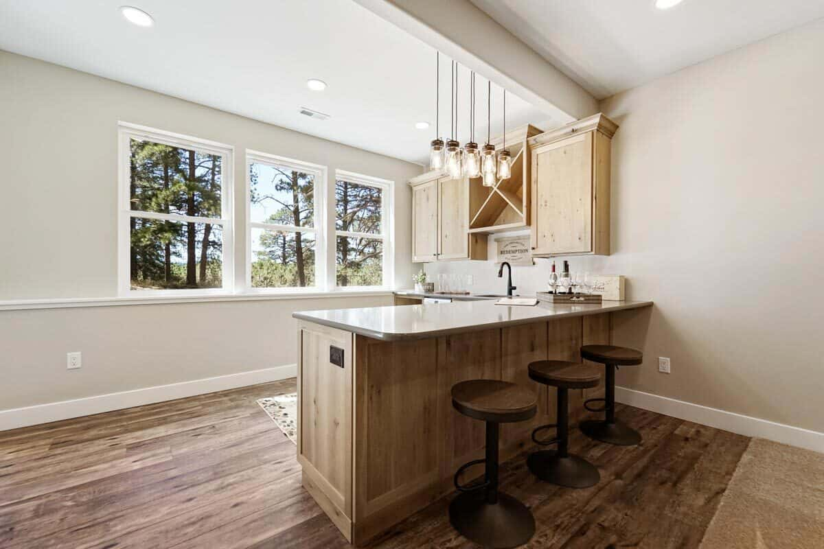 Wet bar with light wood cabinets, glass pendants, and round counter stools.