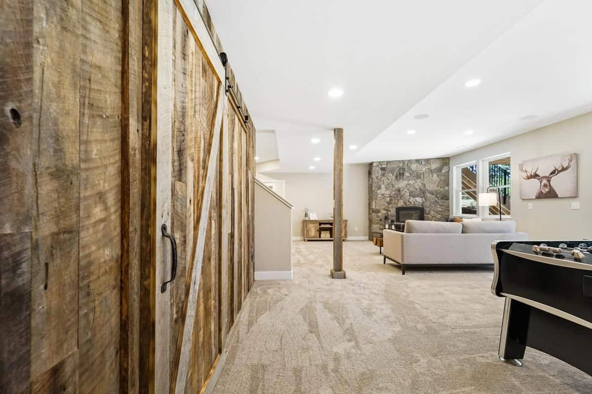 Recreation room with a game area and a living space warmed by a stone fireplace.